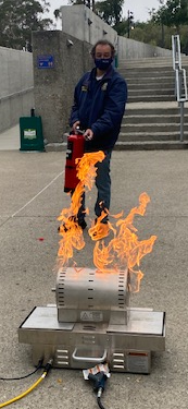 ehs team member using fire extinguisher on live fire prop