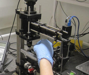 oil being applied to lens of Optical trap set-up on a diode laser