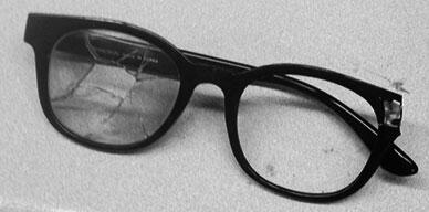 glasses with right lens and temple bar that have been blown away. The left lens is shattered