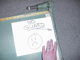 a hand on a paper cutter with no finger guard